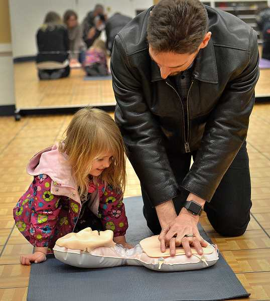 REVIEW PHOTO: VERN UYETAKE - Warren Dabney and his 3-year-old daughter Miriam learn how to perform hands-only CPR during the Emergency Preparedness Fair at Palisades last week. More than 800 people attended the second-annual event in Lake Oswego.