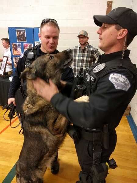 REVIEW PHOTO: ANTHONY MACUK - SRO Bryan Sheldon gets a hug from Charger, the Lake Oswego Police Department's veteran K9, while Officer Vaughn Bechtol looks on. The department celebrated Charger's April retirement by handing out cookies at last week's Emergency Preparedness Fair.