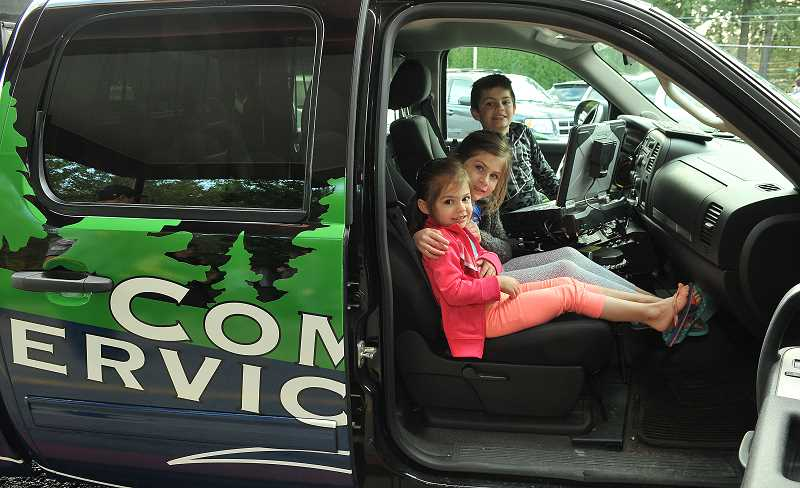 REVIEW PHOTO: VERN UYETAKE - Vivian (from left), Antonia and Jacoby Amandi check out the newly redesigned vehicle used by the Lake Oswego Police Department's community service officers.
