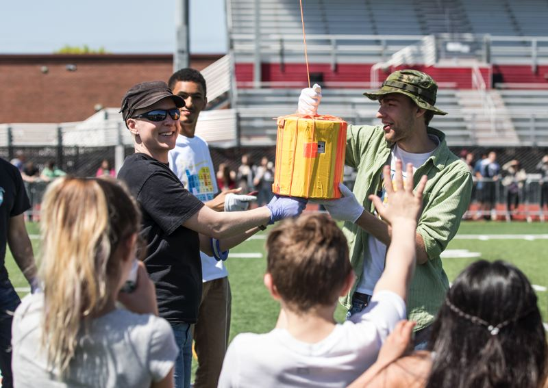 "TIMES PHOTO: JONATHAN HOUSE - Oregon Institute of Technology assistant professor Leif Taylor, left, and student Kack Thomas hold up the ""payload"" of a balloon they tested Monday at Tualatin High School, in anticipation of the total solar eclipse on Aug. 21."
