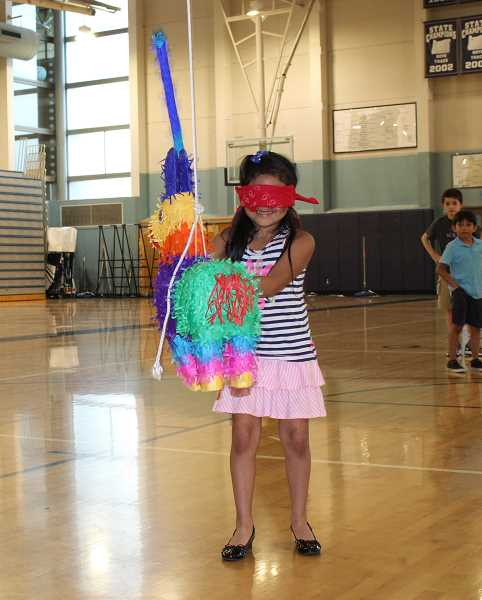 SPOKESMAN PHOTO: ANDREW KILSTROM - Kids took turns taking a whack at pinatas during Wilsonville High's Cinco de Mayo celebration Thursday, May 4.