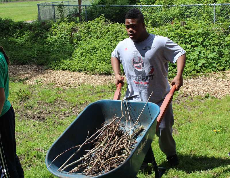 TIDINGS PHOTO: ANDREW KILSTROM - Sadar Muhammed of the Adult Transition Program carries a wheelbarrow of debris out of the way.