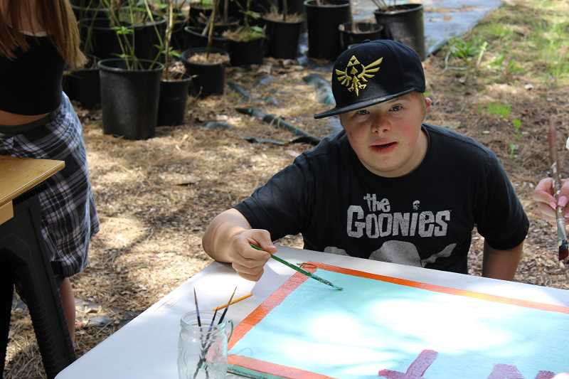 TIDINGS PHOTO: ANDREW KILSTROM - Wilsonville High's Sully Grill helps paint a sign for the new garden kiosk at CREST Headquarters.