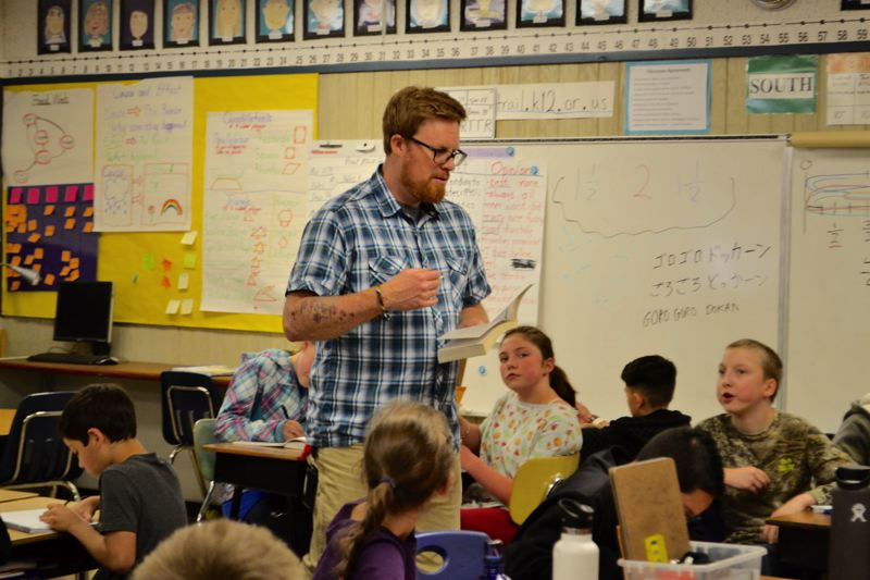 POST PHOTO: BRITTANY ALLEN - Chris Goede reads to his class while they draw their visualizations from the story.