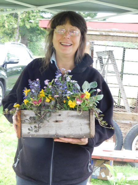 ESTACADA NEWS PHOTO: EMILY LINDSTRAND - Leslie Blewett is all smiles as she displays one of her flower arrangements at the opening day of the Estacada Farmers Market.