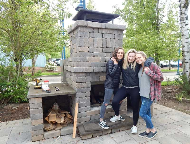 BARBARA SHERMAN - Sherwood High School students (from left) Emma, Madison and Ashlynn pose in front of the outdoor fireplace they helped build in the back yard of the Bowmen House III.
