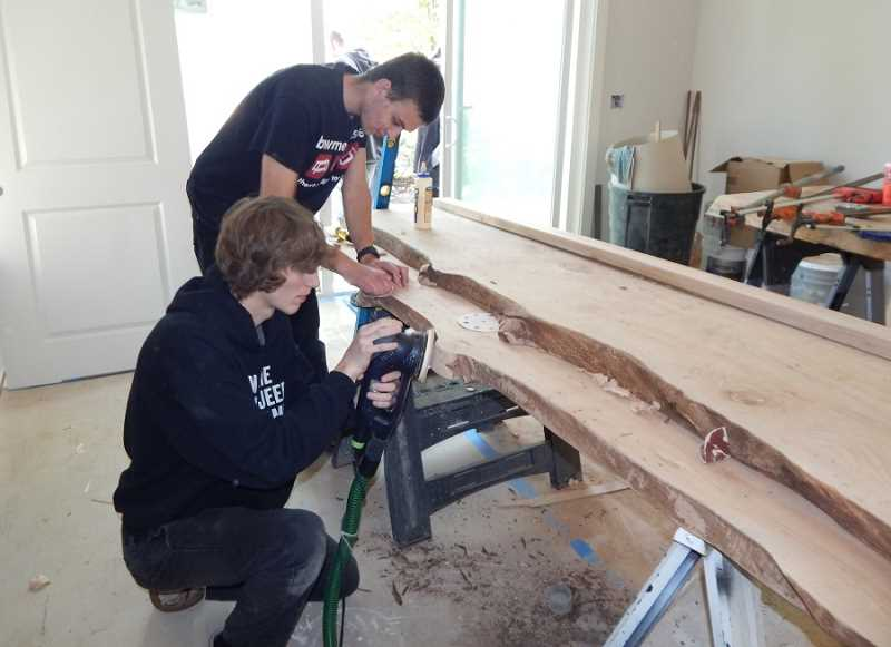 BARBARA SHERMAN - Sherwood High School students (front to back) Ben and Nick work on a beautiful slab of wood destined to be a unique desktop in the office off the Bowmen House entry.