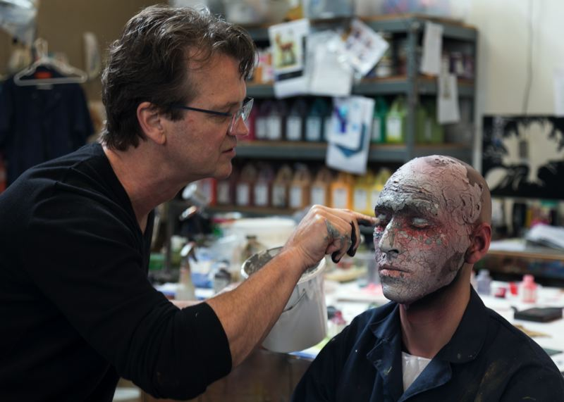 COURTESY: MICHAEL CURRY DESIGN - Michael Curry applies makeup to Orvis Evans as part of preparations for the 'Persephone' production at Oregon Symphony.