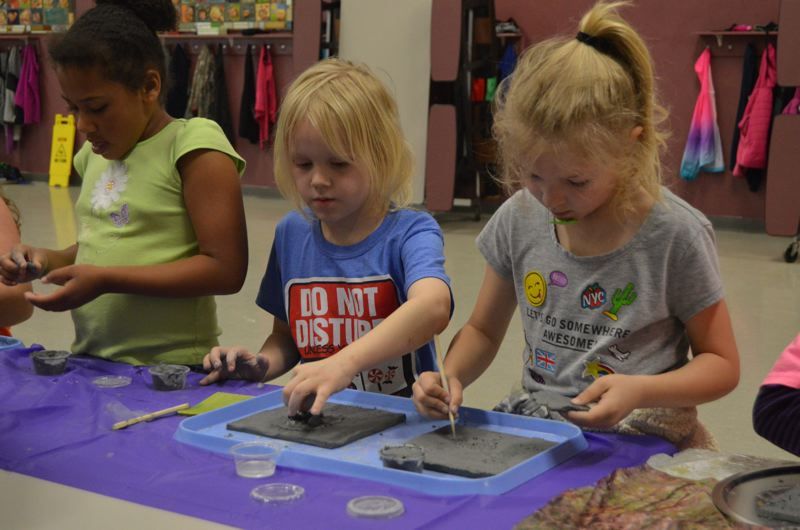 SPOTLIGHT PHOTO: NICOLE THILL - Second-graders Owen Brockmueller and Hailee Mason carve details into the background of their tiles before scoring the clay to attach other pieces to it. The tiles will be fired and then painted by each student.