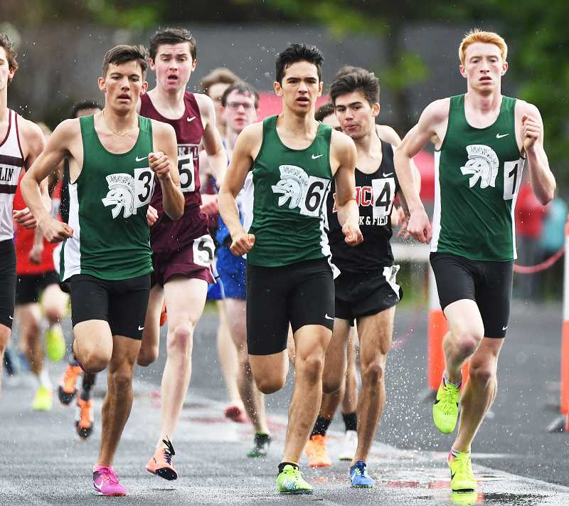 TRIBUNE PHOTO: JOSH KULLA - The Wilson boys won the PIL district track and field title Friday at Franklin High. In the 1,500 meters, Trojan runners (from left) Caleb Seeley, Kian Mitchell and Alex Slenning battled early for the lead.