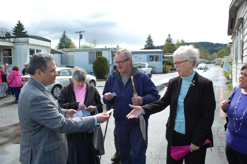 PHOTO BY: RAYMOND RENDLEMAN - State Rep. Mark Meek hands his business card to (from left), Gladstone Mobile Home Park bookkeeper Betty Jean and residents Kim Baller and Judy Dangerfield.