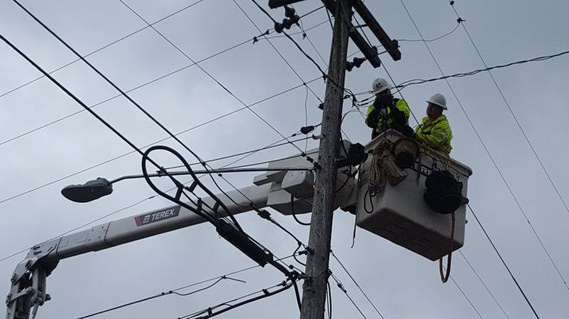 PHOTO BY: TERRY JOHN GIBSON - Employees of Potelco hook up the first LED streetlight fixture along McLoughlin Boulevard in project that will install more than 60 fixures by the end of the year along the corridor from Milwaukie to Gladstone.