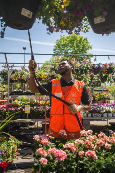 OUTLOOK PHOTO: JOSH KULLA - Elijah Sims has been on the job for barely two weeks at the Home Depot store on Southeast Stark Avenue in Troutdale, part of a spring hiring blitz of some 80,000 workers carried out nationwide by the retail giant. Here, Sims waters flowers in the homes and gardens section of the store.