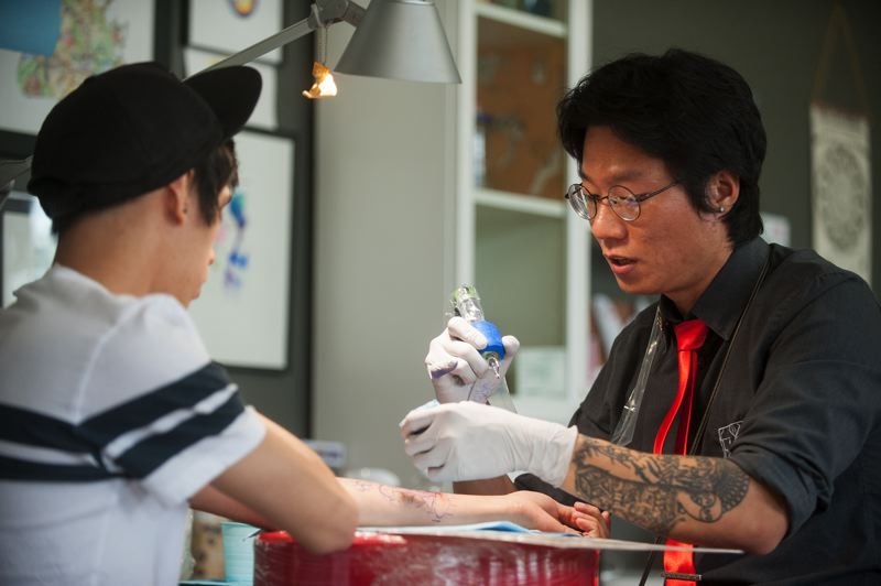 OUTLOOK PHOTO: JOSH KULLA - Tattoo artist Hunmin Ji works on client Chris Kean, a visitor from California, during a recent visit to Equinox Tattoo Collective in downtown Gresham.
