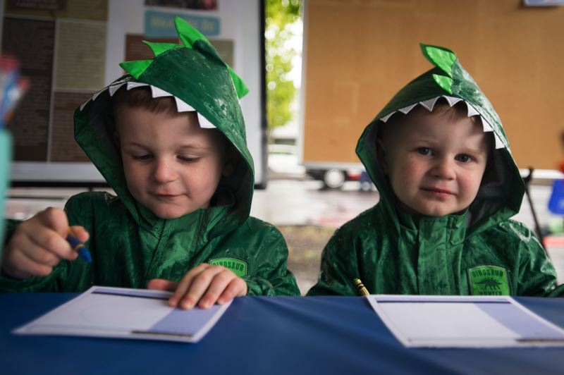 OUTLOOK PHOTO: JOSH KULLA - Connor and Cole Anderson, 3-year-old twin brothers from Troutdale, sit down to color at the Planning and Community Development tent Saturday at the City of Gresham's CityFest event.
