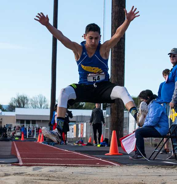 LON AUSTIN/CENTRAL OREGONIAN - Dominic Langley makes a leap in the long jump. Langley finished second in the event with a jump of 20-04.50. Langley was also second in the triple jump, third in the high jump, and ran a leg on the Cowboys' winning 4x400-meter relay team.