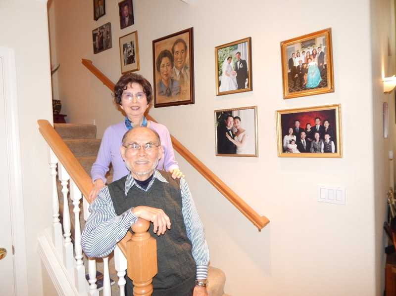 BARBARA SHERMAN - Suzy and Moon Lee stand on the stairs in their Summerfield home with family photos, including their two sons' weddings and grandchildren, on the wall behind them.