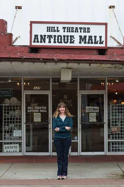 CHRIS OERTELL - Laura Newton stands under the aging Hill Theatre marquee, which will be refurbished thanks to a grant from Oregon Parks and Recreation. Newton, the building owner's daughter, helps run Vintage Variety, another antique store in the same building.