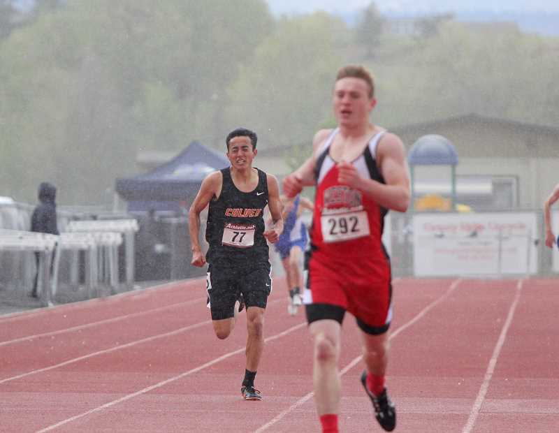 WILL DENNER/MADRAS PIONEER - Culver junior Edwin Gutierrez (left) faced adverse weather in the boys 400, but was able to battle to gut out a second-place finish.