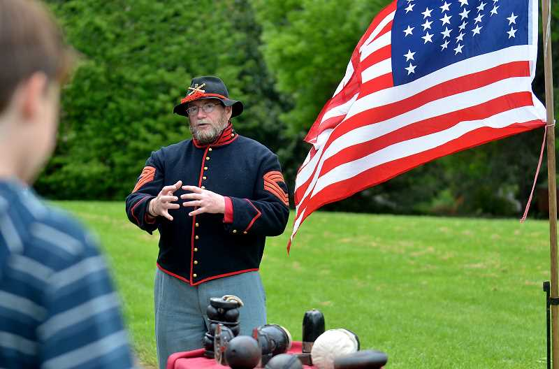 REVIEW PHOTO: VERN UYETAKE - Jack Bentley of Dallas, Ore., explains the different ordinances used with a Civil War cannon.