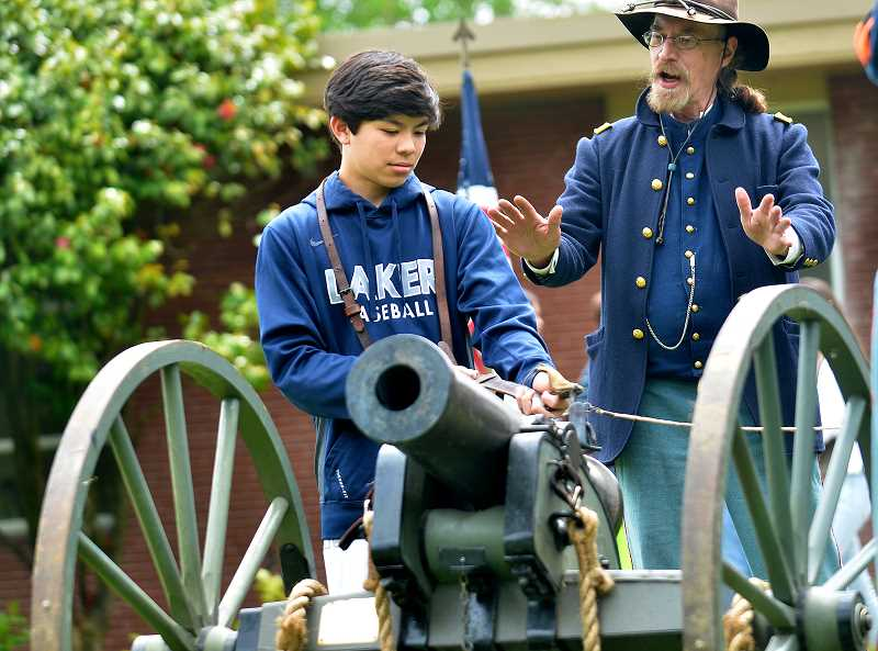 REVIEW PHOTO: VERN UYETAKE - John Beard of Vancouver teaches Lake Oswego Junior High eighth-grader Lucas Wear how to prime the cannon.