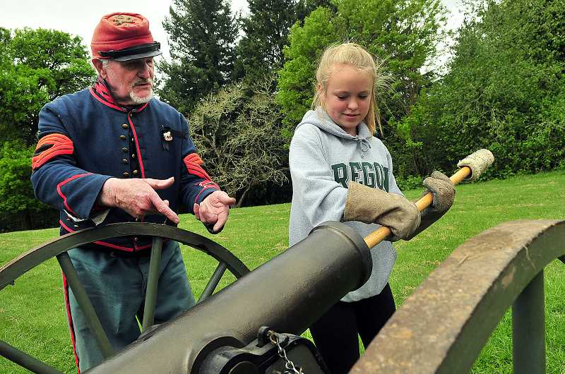 REVIEW PHOTO: VERN UYETAKE - Jack Bentley (left) of Dallas, Ore., shows eighth-grader Olivia Hanson how to use the worm to clean the barrel of the cannon between firings.
