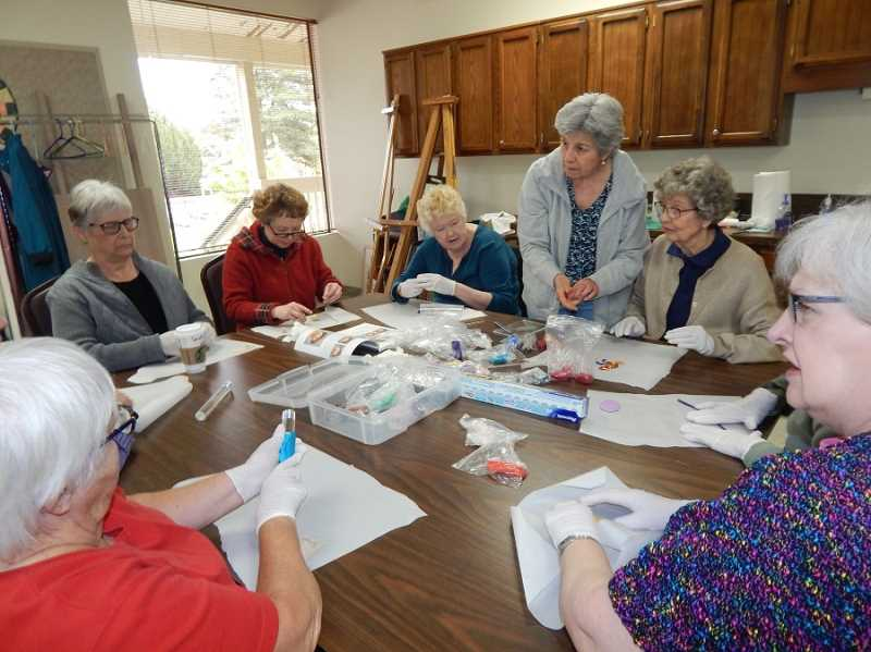 BARBARA SHERMAN - Summerfield Craft Club members working on their polymer clay projects include Susan Burson (third from left) creating a head and Bonnie Crismon (second from right) making a rooster with help from teacher Lydia Cooper (third from right).
