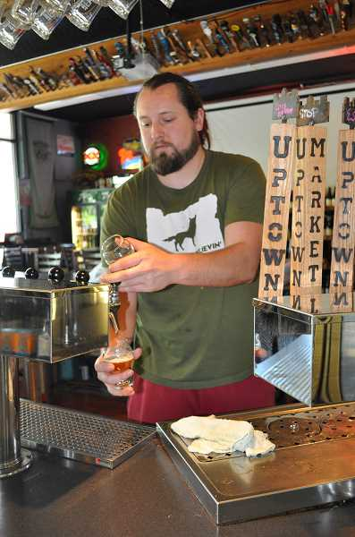 BLAIR STENVICK - Head brewer Tyler Staples pours an IPA taster at Uptown Market in Beaverton.