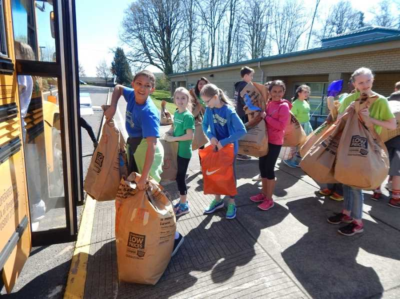 BARBARA SHERMAN - Deer Creek Elementary student ambassadors toted big bags filled with clothes and other items donated by all the students from the school lobby out to the waiting bus, where Tigard High School students waited inside to 'stuff the bus.'