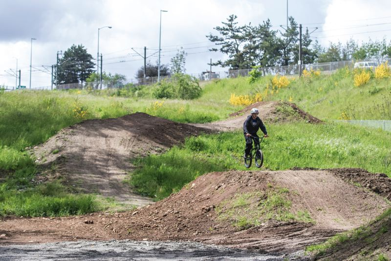 TRIBUNE PHOTO: JONATHAN HOUSE - Anthony Maldonado tests out the bike jumps at the Dirt Lab at Gateway Green. The mountain biking features at the park open June 24.