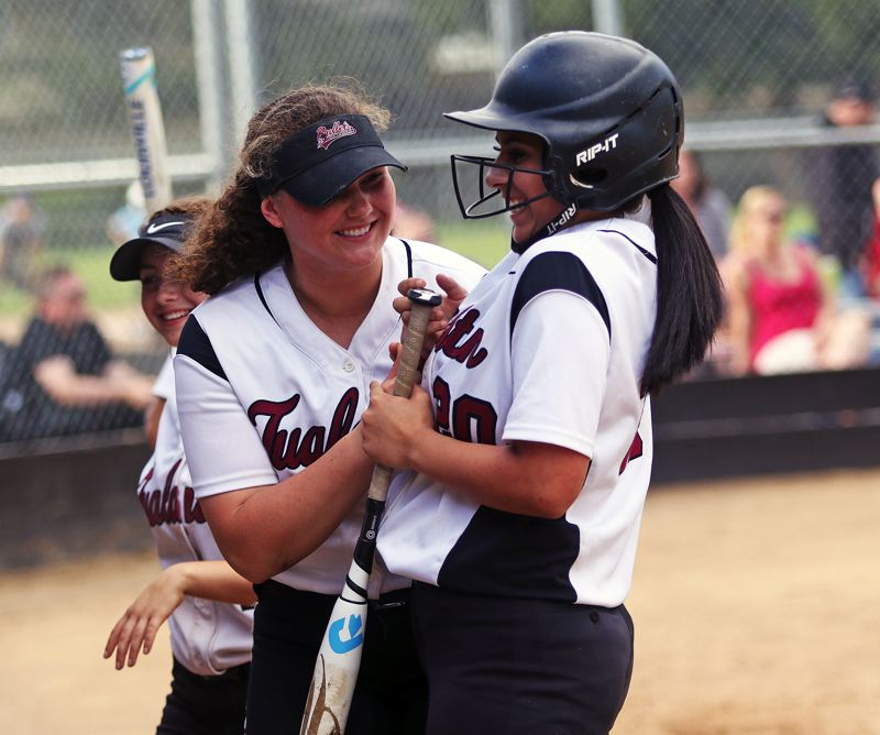 DAN BROOD - Tualatin High School sophomore Emily Johansen (left) greets junior Zoe Olivera outside the dugout following Olivera's sixth-inning home run. Johansen also hit a home run for the Wolves in the 15-3 win at Sherwood.