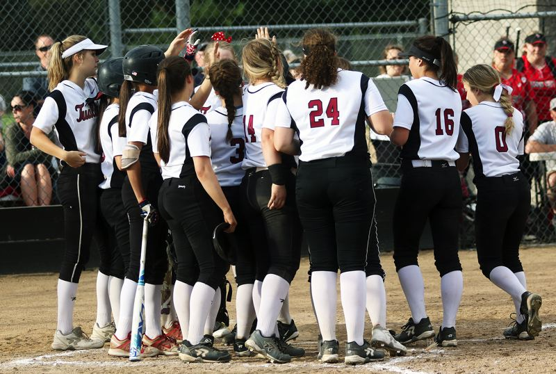 DAN BROOD - The Tualatin High School softball team gathers at home plate to greet Zoe Oliera following her home run at Sherwood.