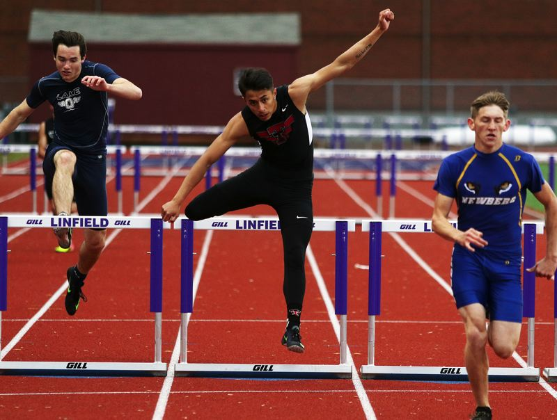 DAN BROOD - Tualatin senior Ryan Cavinta (center) gets over the final hurdle on his way to placing second in the 300 intermediate hurdles event at the TRL disrict meet.