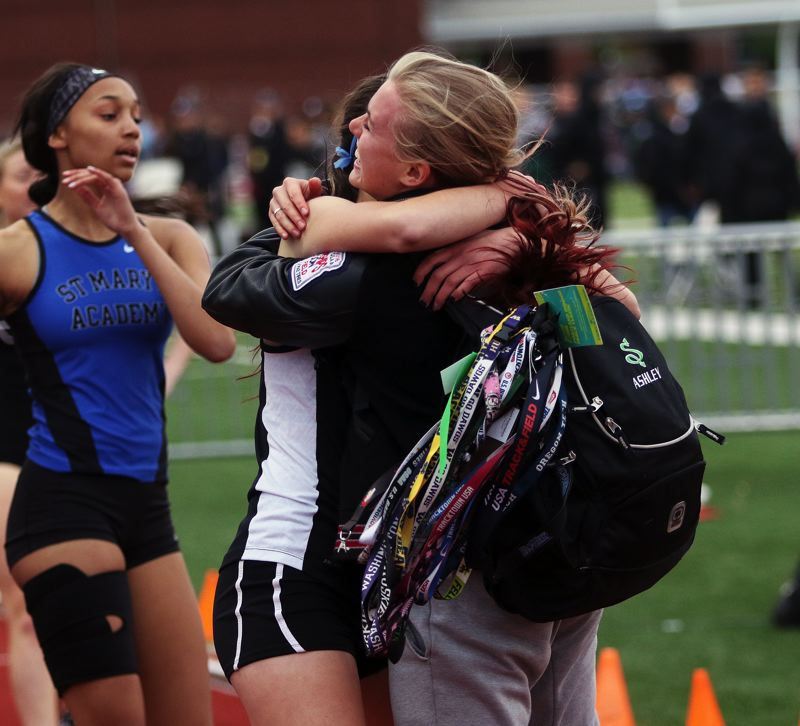 DAN BROOD - Tualatin senior Ashley Slater (right) greets Kennedy Oleson following Oleson's victory in the 300 intermediate hurdles.