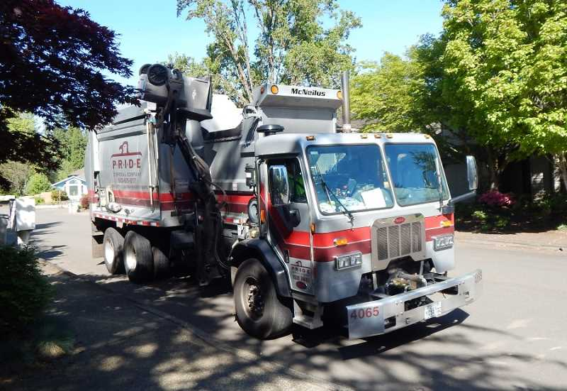 BARBARA SHERMAN - A Pride Dispoal truck picks up a gabage cart in Tigard, which is a familar sight in King City on Mondays; however, the King City City Council has approved changes to the company's rates and service options.