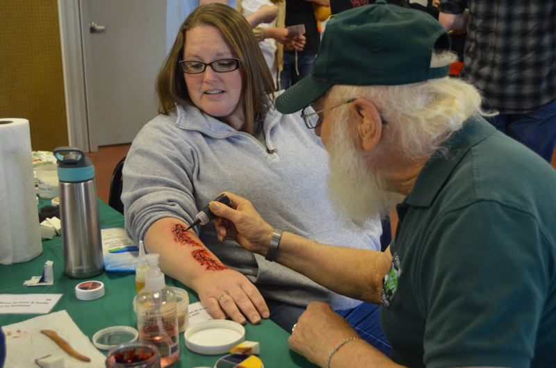 SPOTLIGHT PHOTO: NICOLE THILL - Sarah Cluff, left, reacts to a realistic looking arm wound fashioned out of makeup, that was applied by CERT volunteer Joe Errante. Cluff and her daughter, Shelby, both volunteered to play victims in the training for the first time this year.