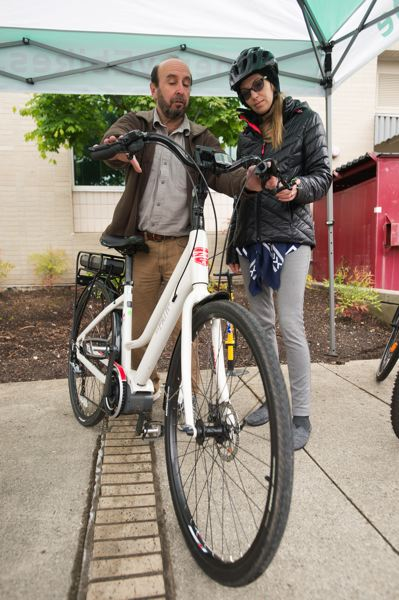 OUTLOOK PHOTO: JOSH KULLA - Rich Fein, owner of Cynergy E-Bikes of Portland, shows city of Gresham employee Shaunna Sutcliffe the ins and outs of how to operate the bike Wednesday. The company set up a booth offering test rides and slices of pizza outside Gresham City Hall, prompting a string of staffers to take up the offer.