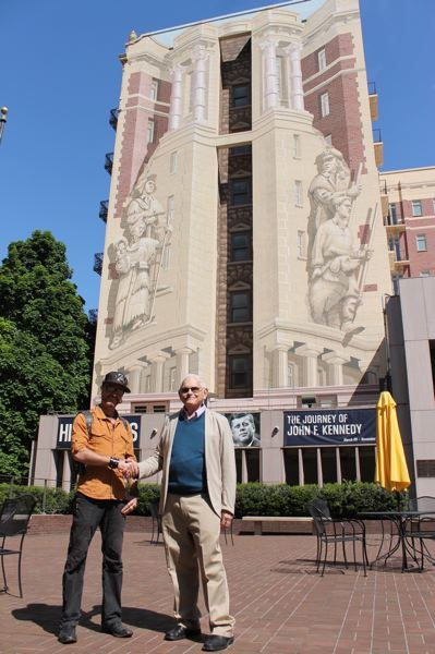TRIBUNE PHOTO: LYNDSEY HEWITT - Artists Dan Cohen, left, and Richard Haas, stand in front of the mural painted on the Sovereign Hotel. Haas painted the original mural in 1989 while Cohen recently restored it.