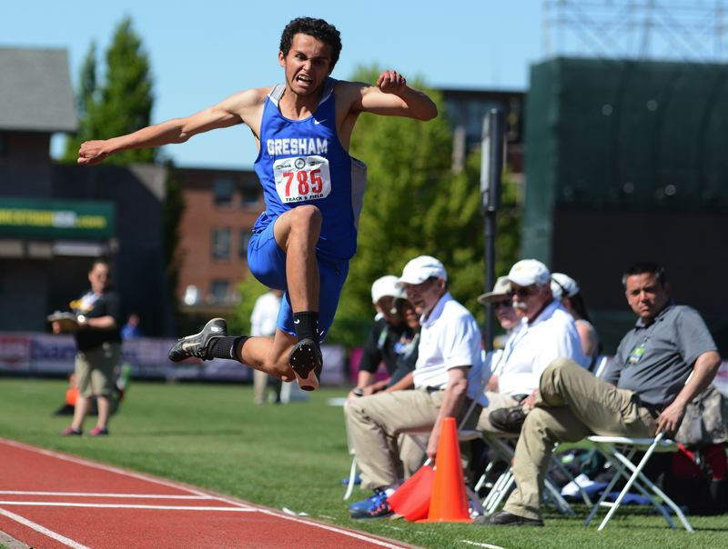 OUTLOOK PHOTO: DAVID BALL - Gresham senior Joseph Harris soars toward the pit on his way to a win in the triple jump, moving to the top of the leader board on his final attempt.