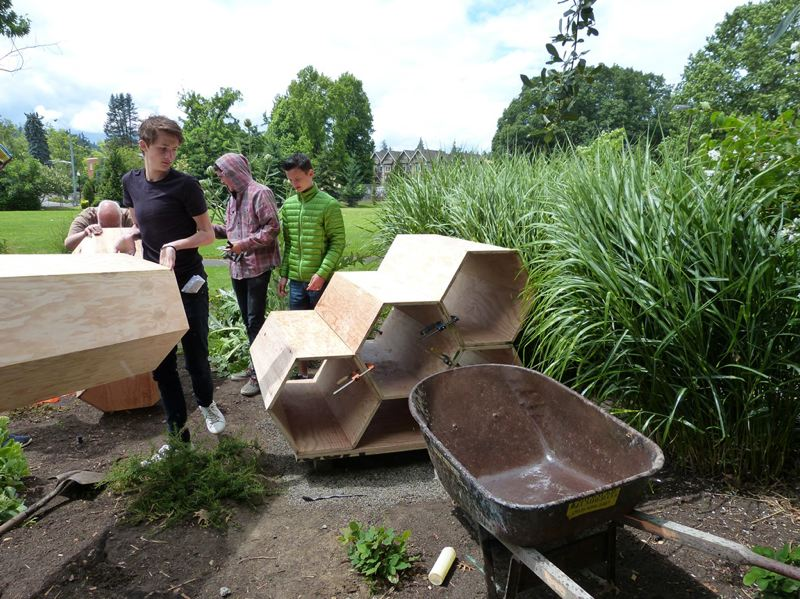 PHOTO BY: KELLY HOGAN - Waldorf 11th-graders, from left, Bjorn Johansson, Jalen DeSantis and Jason Hardy, build a pollinator hotel with woodworking teacher Tom Myers.