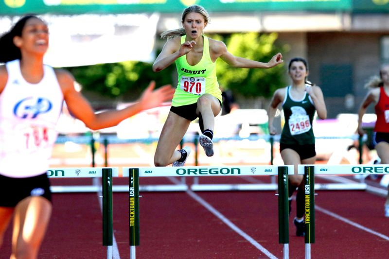 TRIBUNE PHOTO: JONATHAN HOUSE - Jesuit High's Claire Corbitt (center) comes down the straightaway near the end of the Class 6A girls 300-meter hurdles, with Wilson's Emma Swanson (right) further back.