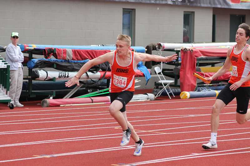 PIONEER PHOTO: CONNER WILLIAMS - Molalla sophomore Treyton Bierly (left) reaches for the baton from junior Michael House during the 4x100