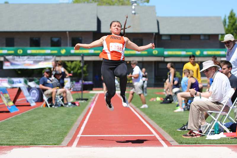 PAMPLIN MEDIA GROUP PHOTO: JIM BESEDA - Molalla senior Desirae DesRosiers leaps into the air in the Long Jump at the state meet Friday. DesRosiers took bronze in the event with a PR mark of 17 feet, three inches.