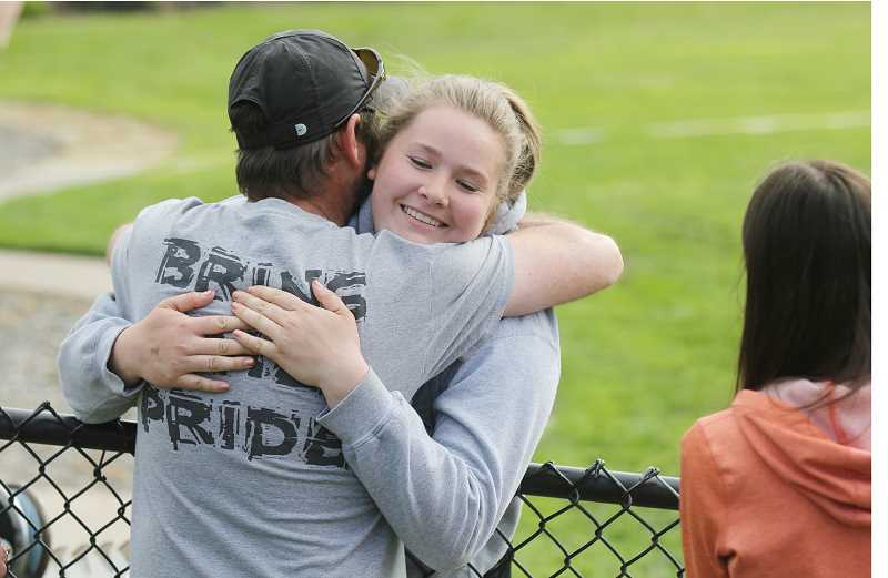WILL DENNER/MADRAS PIONEER - Culver junior Catylynn Duff (right) hugs her coach, Mike Dove, after she won the 2A girls discus state title with a record-breaking throw of 138 feet, 7 inches in her last attempt of Thursday's competition at the State Track and Field Championships in Eugene.