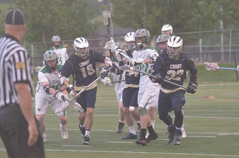 HERALD PHOTO: COREY BUCHANAN -  Canby lacrosse players Aaron Kromer (10) and Jacob Huggins chase after a loose ball.
