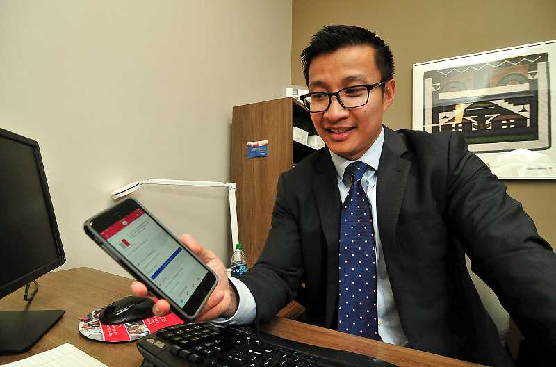 STAFF PHOTO: VERN UYETAKE - Nathan Nguyen, Bank of Americas regional sales executive for Washington and Oregon, uses the banks smartphone app.
