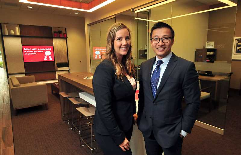 STAFF PHOTO: VERN UYETAKE - Bank of Americas Lake Grove Financial Center Manager Ashley Troutt, left, and regional sales executive for Washington and Oregon Nathan Nguyen show off the banks newly renovated building.