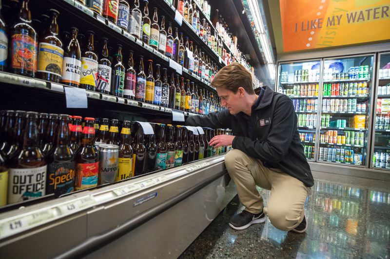 PAMPLIN MEDIA GROUP: JONATHAN HOUSE - Silas Akin stocks beer at the new Market of Choice in the Goat Blocks.