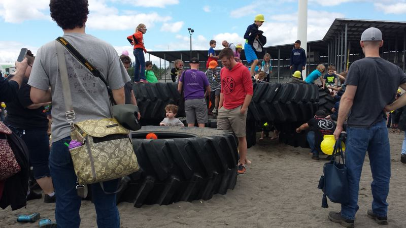 PAMPLIN MEDIA GROUP: JOSEPH GALLIVAN  - Nathan Ofstad (red hoodie) is in the wine bottling trade but came from Oregon City with his wife and son because the latter is obsessed with bulldozers and cranes. Here Ofstad watches his son playing on some tractor tires.