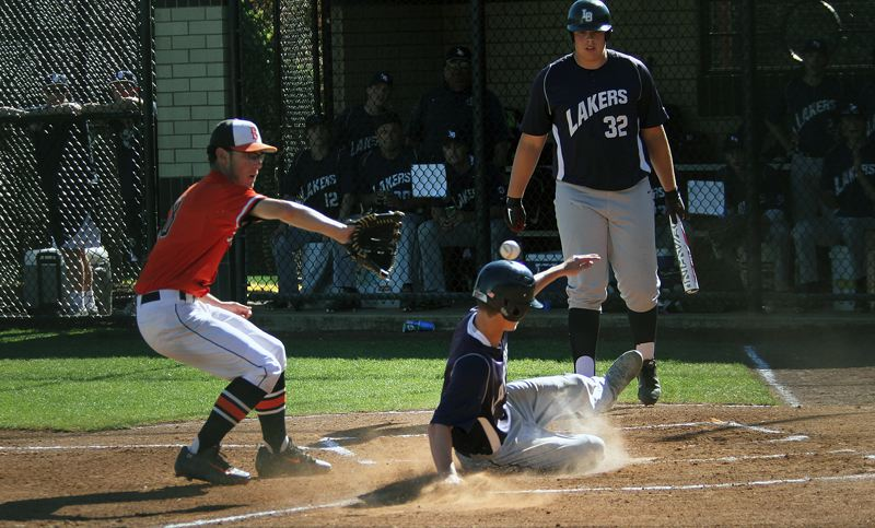 PMG PHOTO: MILES VANCE - Lake Oswego's Jake Dukart slides home to score in front of Beaverton's Callan McRae in the first inning of the Beavers' 9-6 win over the Lakers in the Class 6A state quarterfinals at Beaverton High School on Friday.